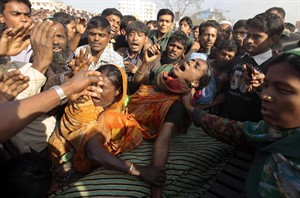 Relatives cry near the body of Josna, 16, a victim of a fire at a two-storied garment factory in Dhaka, Bangladesh, Saturday, Jan. 26, 2013. The fire killed at least six female workers and injured another five, police and fire officials said. The latest fire occurred more than two months after a deadly fire killed 112 workers in another factory near the capital city, raising questions about the safety measures in Bangladesh garment industry. (AP Photo/A.M. Ahad)