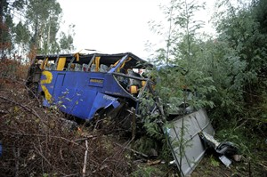 The wreckage of a bus which ran off the road and crashed into a ravine, killing 10 people and injuring 33 is seen in Serta, central Portugal, Sunday, Jan. 27, 2013. National Civil Protection authority spokesman Carlos Guerra says the injured have been taken to hospitals in the cities of Coimbra and Castelo Branco. (AP Photo/Sergio Azenha) PORTUGAL OUT