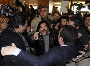 Diego Armando Maradona makes his way through journalists as he arrives in Naples, Italy, Monday, Feb. 25, 2013. Maradona is in Naples to attend a TV show and a press conference. (AP Photo/Salvatore Laporta)