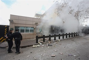 Two police officers arrive at Gate 2 of the US embassy just minutes after a suicide bomber has detonated an explosive device at the entrance of the U.S. Embassy in the Turkish capital, Ankara, Turkey, Friday, Feb. 1, 2013, At least two people are dead, officials said. An Associated Press journalist on Friday saw a body in the street in front of an embassy side entrance. (AP Photo/Yavuz Ozden, Milliyet) TURKEY OUT - INTERNET OUT