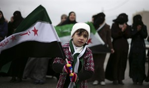 """A girl waves the revolutionary Syrian flag during a protest against President Bashar Assad in front of the Syrian embassy to commemorate the 31st anniversary of the 1982 Hama massacre, in the era of Hafez Assad, in Amman, Jordan, Friday, Feb. 1, 2013. The Arabic writing on the flag reads """"free Syria."""" (AP Photo/Mohammad Hannon)"""